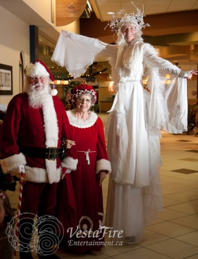 stilting angel with Santa and Mrs Clause