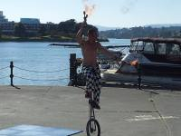 Fire juggler on unicycle entertains at Victoria Inner Harbour